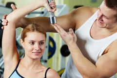 Portrait of sporty woman doing exercise with dumbbell and her trainer supporting Stock Photos