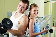 portrait of sporty couple with dumbbells smiling at camera - stock photo
