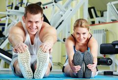Stock Photo of portrait of sporty couple doing physical exercise and smiling at camera