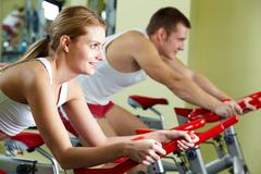Portrait of sporty couple doing physical exercise on special equipment Stock Photos