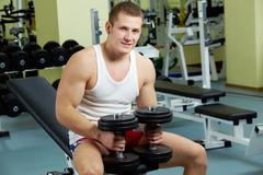 portrait of sporty man with dumbbells looking at camera in gym - stock photo