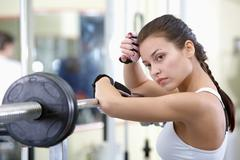 photo of fit brunette with weightlifting device near by - stock photo