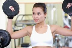 photo of fit brunette with bars for weight in sport gym - stock photo