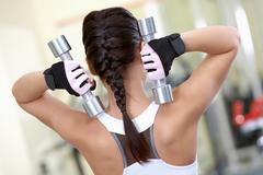 rear view of young female with dumbbells doing exercises in gym - stock photo