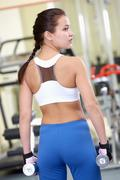 rear view of young female with dumbbells during sport practice in gym - stock photo