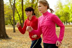 Two young women jogging in autumn park Stock Photos