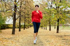 Girl running among autumn trees and smiling Stock Photos