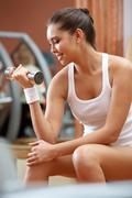 portrait of young female with dumbbells doing exercises for strong arms - stock photo