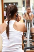 Rear view of sporty girl talking by the mobile phone in gym Stock Photos