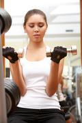 portrait of young female doing physical exercises in gym - stock photo