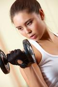 portrait of young female doing exercises with barbell in gym - stock photo
