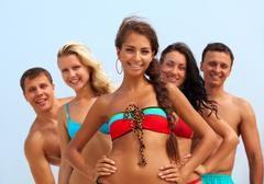 portrait of happy girl in bikini looking at camera with friends behind - stock photo