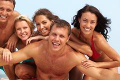 Portrait of joyful guy and happy girls in bikini on background looking at camera Stock Photos