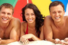 Portrait of happy girl between two guys lying on sand on summer vacation Stock Photos