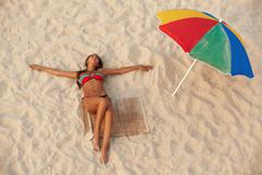 Photo of pretty girl in swimsuit lying on sandy beach with colorful beach umbrel Stock Photos