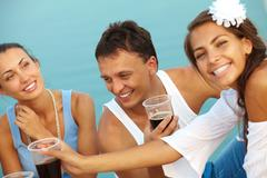 Image of happy guy with drink surrounded by girls at beach party Stock Photos