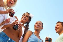 Image of happy friends with drinks having fun at beach party Stock Photos