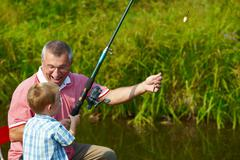 photo of grandfather and grandson fishing in summer - stock photo