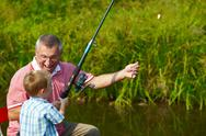 Stock Photo of photo of grandfather and grandson fishing in summer