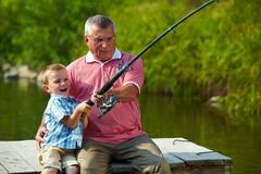 Photo of grandfather and grandson pulling rod while fishing on weekend Stock Photos