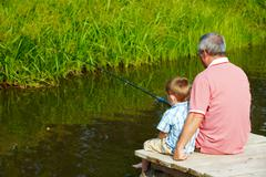 photo of grandfather and grandson sitting on pontoon and fishing on weekend - stock photo