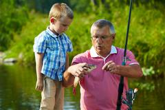 Photo of grandfather and grandson looking at fish caught by them Stock Photos