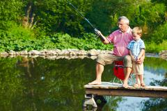 photo of grandfather and grandson on pontoon fishing on weekend - stock photo
