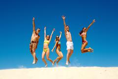 Happy group of young jumping people with hands up Stock Photos