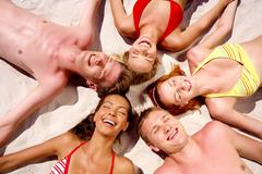 Photo of smiling people lying in the circle on the sand Stock Photos