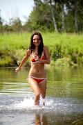 Portrait of slim woman wearing swimsuit running in the lake Stock Photos