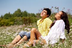 portrait of attractive man and woman relaxing on the   glade - stock photo