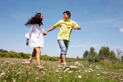 portrait of woman and man holding by hands and walking over the glade - stock photo