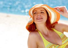 close-up of pretty lady in hat on the seaside - stock photo