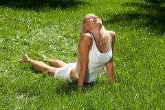 above view of pretty blonde lying on green grass and enjoying fine summer day - stock photo