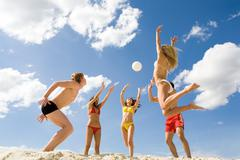 Photo of five friends playing with ball on sand Stock Photos