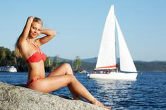 portrait of beautiful blonde sitting by the sea on background of blue water - stock photo