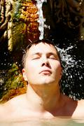 portrait of young man under stream of water taking pleasure - stock photo