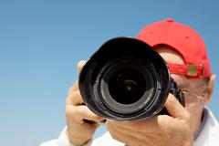 close-up of photograpther taking shots against blue sky - stock photo