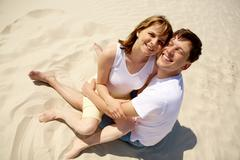 Portrait of amorous couple embracing while sitting on sand Stock Photos
