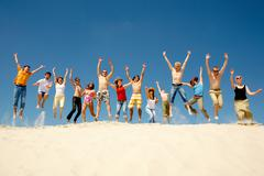 Crowd of friends jumping on sandy beach with their arms raised against blue sky Stock Photos