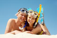 portrait of cheerful couple in aqualungs looking at camera with smiles - stock photo