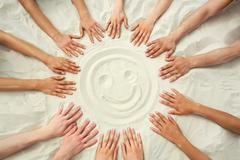 photo of smiling face hands painting on sand surrounded human hands - stock photo
