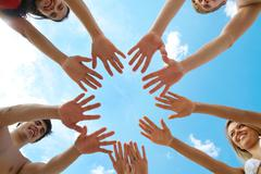 Circle of people' hands on blue sky background Stock Photos