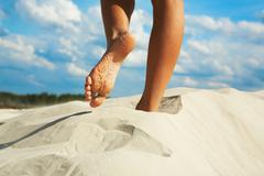 Close-up of woman going barefoot over sandy beach Stock Photos