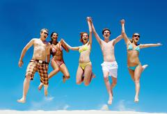 Joyful team of friends jumping on sandy beach and shouting Stock Photos