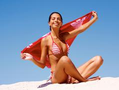Photo of young luxurious woman sitting on sandy beach with towel Stock Photos