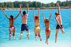 Rear view of friends jumping into water during summer vacation Stock Photos