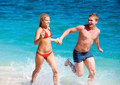 portrait of happy couple running together during summer vacation - stock photo