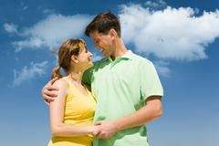 Photo of amorous couple smiling at each other on background of bright sky Stock Photos