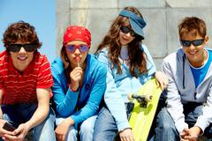 row of several teens in sunglasses looking at camera - stock photo